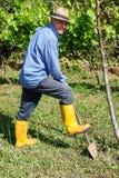 Stivali gialli dell'agricoltore che lavorano il giacimento della vanga Immagine Stock