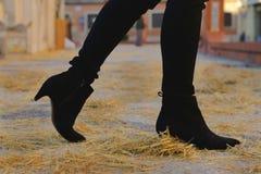 Stivali neri della caviglia del tallone che camminano sulla paglia gialla immagine stock