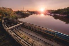 Stivali sul fiume nel tramonto immagine stock