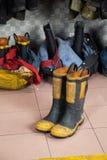 Stivali sul pavimento alla caserma dei pompieri Fotografie Stock Libere da Diritti