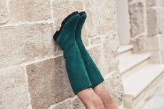 Stivali verdi sui piedi della donna che si appoggiano parete di pietra Immagine Stock