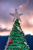 Stjärna överst av julgranen mot solnedgånghimmel arkivfoto