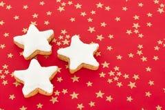 Stjärna formade kanelbruna kexar på röd bakgrund Royaltyfri Foto