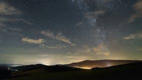 Stjärnahimmel med galaxen för mjölkaktig väg och moln som flyttar sig över härlig landskaptidschackningsperiod lager videofilmer