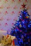 Stjärnan dekorerade överst julgranen med närvarande askar inom hus arkivbild