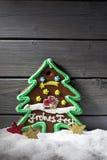 Stjärnan för pepparkakajulträdet formade garneringar på hög av snö mot träbakgrund Arkivfoto
