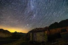 Stjärnaslingor och isolerat hus i Schweiz fjällängar arkivfoton