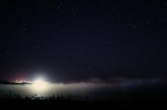 Stjärnklar himmel över dimmigt landskap Arkivbild