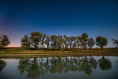Stjärnklar himmel för blå natt ovanför sjöfloden Glödande stjärnor för natt och trädträn reflekterade i vatten Royaltyfri Foto