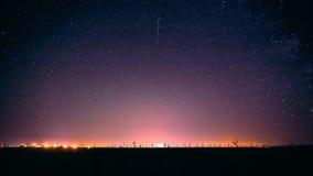 Stjärnklar himmel för färgrik natt ovanför de gula stadsljusen Glödande stjärnor för natt Royaltyfria Bilder