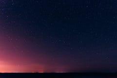 Stjärnklar himmel för färgrik natt ovanför de gula stadsljusen Natt Gl Arkivfoton