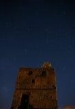Stjärnklar himmel för natt över ett övergett stentorn En fallande stjärna är synlig En djup mörk natt Arkivfoton