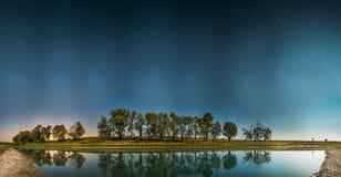 Stjärnklar himmel för natt ovanför sjöfloden Glödande stjärnor och träd för natt Royaltyfri Fotografi
