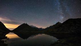 Stjärnklar himmel för VintergatanTid schackningsperiod utöver den snowcapped bergkanten, reflekterad på den idylliska apinesjön stock video