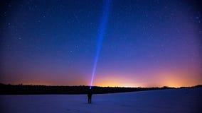 Stjärnklar himmel och man med ficklampan var kan planlägga den din använda vintern för illustrationligganden natten Royaltyfri Foto