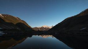 Stjärnklar himmelnatt och tidschackningsperiod för mjölkaktig väg över bergdalen och en sjö arkivfilmer