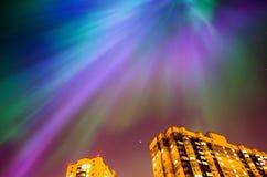 Stjärnklar natt för norrsken över staden och husen Arkivbild