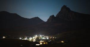 Stjärnor över nattbergdalen med ljus av byn stock video