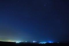 Stjärnor över staden på natten. Arkivbilder