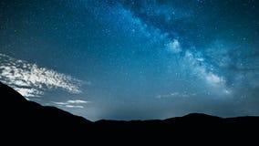 Stjärnor för natthimmel med den mjölkaktiga vägen över berg arkivbild