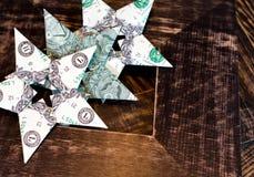 Stjärnor för origami för dollarräkningar på gammalt trä inramar bakgrund Royaltyfri Foto