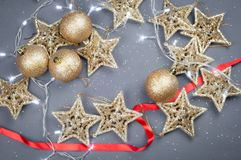 Stjärnor och bollar för julleksaker guld- på en grå bakgrund royaltyfri fotografi