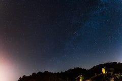 Stjärnor och fallande stjärna över skogen och ett hus på Troodoen Royaltyfria Foton