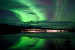 Stjärnor och nordliga lampor över den mörka vägen på laken Arkivfoton