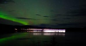 Stjärnor och nordliga lampor över den mörka vägen på laken Royaltyfria Bilder