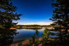 Stjärnor och sjö vid månsken på vallbehållaren Arkivbilder