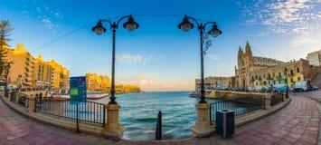 StJulian ` s,马耳他-美丽的Balluta海湾与我们的夫人迦密山教会的早晨  库存图片