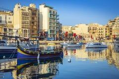StJulian ` s, Malta - Kolorowe Luzzu łodzie rybackie przy Spinola trzymać na dystans Zdjęcia Stock