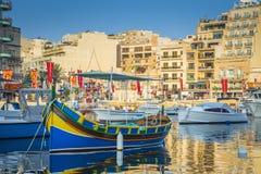 StJulian ` s, Malta - Kolorowe Luzzu łodzie rybackie przy Spinola trzymać na dystans Obrazy Royalty Free
