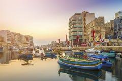 StJulian ` s, Malta - Tradycyjne kolorowe Luzzu łodzie rybackie przy Spinola trzymać na dystans Zdjęcie Royalty Free