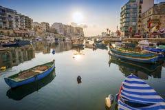 StJulian ` s, Malta - wschód słońca przy Spinola zatoką z Tradycyjnymi maltese łodziami rybackimi Zdjęcie Royalty Free
