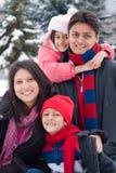 Östlig indisk familj som leker i snowen Arkivbilder