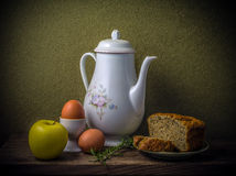 Stll life. A still life photo. The set consist of an apple, eggs, a kettle, rosemary and bread Stock Image
