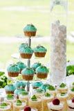 Ställning för bröllopmuffintorn med turkoskakor Arkivfoton