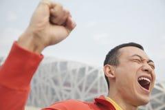 Stäng sig upp av beslutsam ung man i idrotts- kläder med näven i luften, med modern byggnad i bakgrunden i Peking, chien Royaltyfri Foto