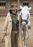 Stäng sig upp av en Cowboy som plattforer bredvid hans häst Royaltyfri Foto