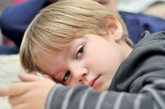 Stäng sig upp av en gullig ung pojke som ligger på säng Royaltyfri Foto
