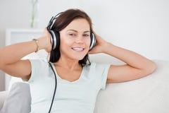 Stäng sig upp av en älskvärd brunett som lyssnar till musik Royaltyfri Foto