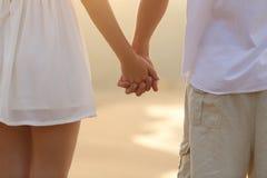 Stäng sig upp av ett par som går och rymmer händer på stranden Arkivfoton