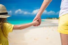 Stäng sig upp av fadern och den lilla dottern som rymmer sig händer på stranden Fotografering för Bildbyråer
