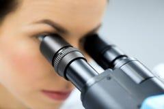 Stäng sig upp av forskaren som ser till mikroskopet i labb Arkivfoto