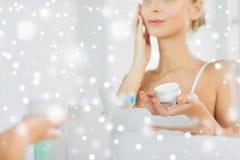 Stäng sig upp av kvinnan som applicerar framsidakräm på badrummet Royaltyfri Bild