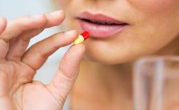 Stäng sig upp av kvinnan som tar medicin i preventivpiller Fotografering för Bildbyråer