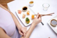 Stäng sig upp av kvinnan som äter sushi på restaurangen Arkivfoton