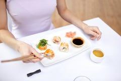 Stäng sig upp av kvinnan som äter sushi på restaurangen Royaltyfri Foto