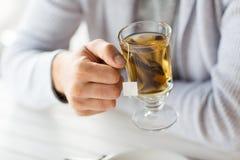 Stäng sig upp av mannen som hemma dricker te eller kafét Arkivfoton